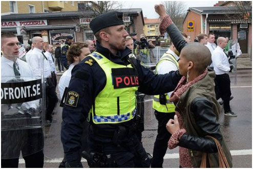 Bravura: Tess Asplund enfrenta os nazistas enquanto marcham pelas ruas de Borlänge (Suécia) antes de ser separada pela polícia.