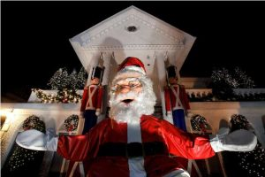 A large Santa Claus sits at the entrance of a decorated house at the Dyker Heights Christmas Lights in the Dyker Heights neighborhood of Brooklyn, New York City, U.S., December 23, 2016. REUTERS/Andrew Kelly - RTX2WCOR